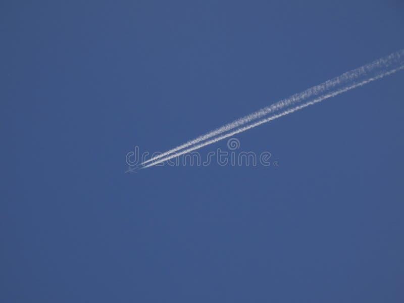 Plat sillonnant le ciel bleu et laissant un sillage blanc photo stock