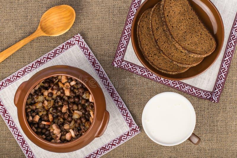 Plat traditionnel letton - pois gris avec le lard, le pain de seigle et le képhir image stock