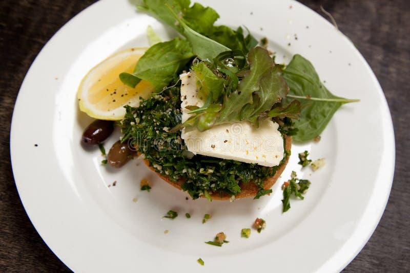 Plat végétarien avec le taboulé, le feta, la fusée, les olives et l'arrangement de citron sur un tarte de potiron image stock