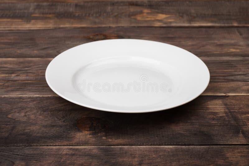 Plat vide blanc sur la table en bois foncée photo libre de droits