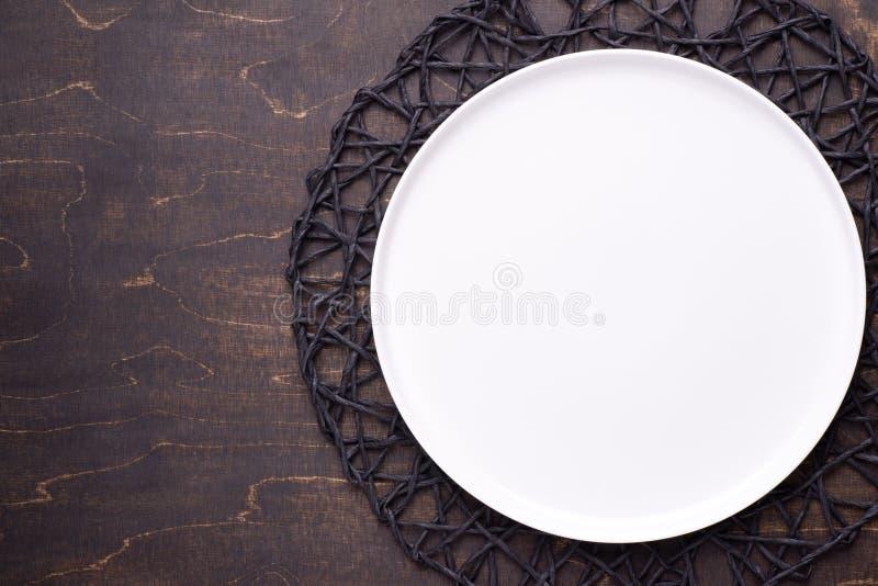 Plat vide blanc sur la table en bois fonc image stock
