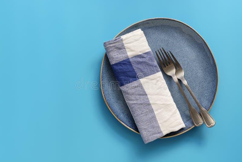 Plat vide bleu, serviette à carreaux et fourchettes sur le fond bleu en pastel Vue sup?rieure, configuration plate, l'espace de c photographie stock