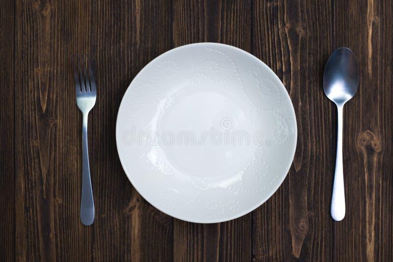 Plat vide ou plat blanc avec la cuillère et fourchette sur le Ba en bois de table photographie stock