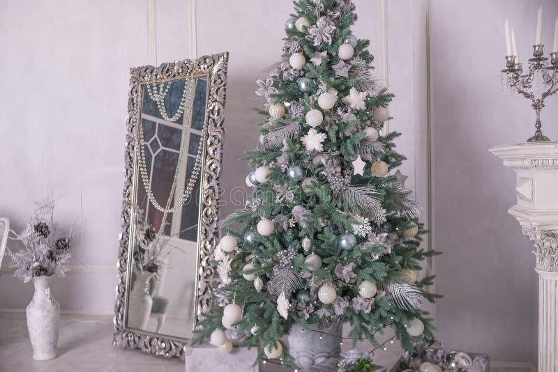 Plata grande y árbol de navidad adornado blanco con los regalos en interior de lujo Año Nuevo en el país La Navidad interior con imagen de archivo libre de regalías