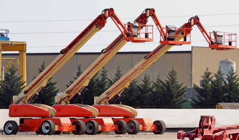 A plataforma aérea do grande trabalho três alinhou em um local industrial imagens de stock