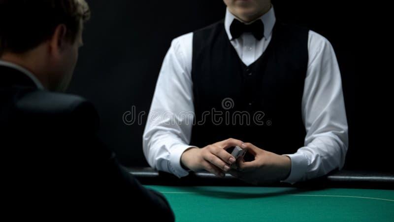 Plataforma da terra arrendada do crouoier do casino de cartões na tabela verde para o cliente, jogo de pôquer fotografia de stock royalty free