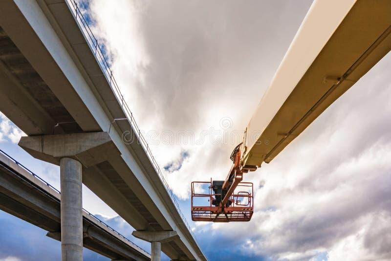 Plataforma de elevación en la construcción y la reparación de un puente de la carretera fotos de archivo