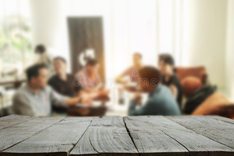 Plataforma de espacio de madera del escritorio con los hombres de negocios en una reunión en la oficina imagenes de archivo