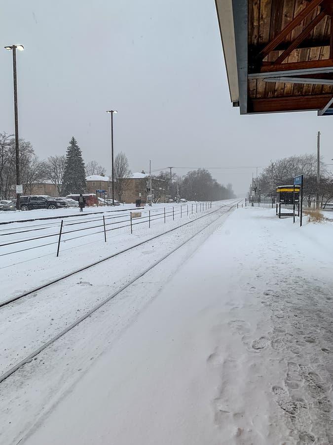 Plataforma de la estación de tren en los suburbios de Chicago durante nevada, con el viajero caminando a lo largo de vías foto de archivo
