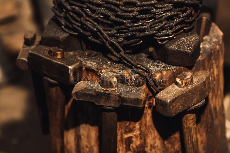 Plataforma de madeira do close up com batente, corrente e martelos fotografia de stock