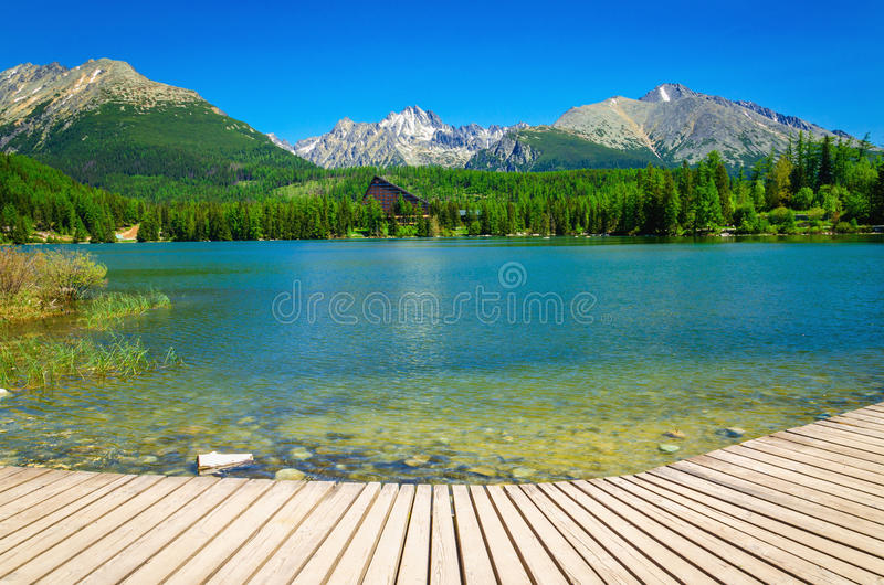 Plataforma de madera con la visión en el lago claro de la montaña foto de archivo