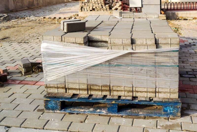 Plataforma de madera con las piedras grises del pavimento en el sitio de las obras viales Reparación de la acera en una calle de  fotografía de archivo libre de regalías