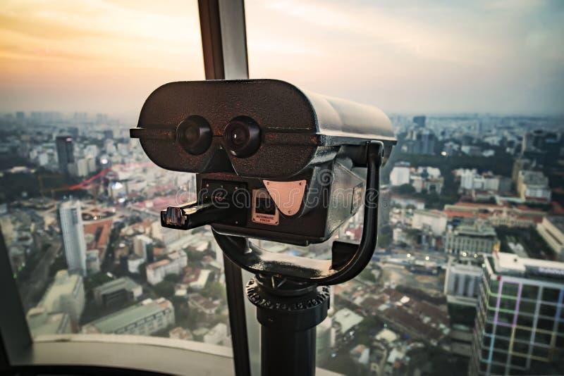 Plataforma de observación en el edificio alto con los prismáticos grandes para observar el panorama hermoso de la ciudad de Saigo imagenes de archivo
