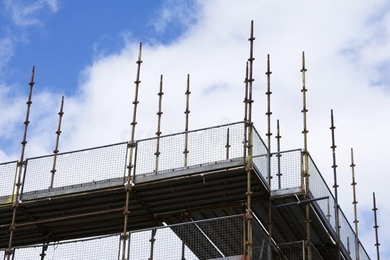 Plataforma e polos de andaime no céu azul no nível elevado de terreno de construção da construção foto de stock royalty free