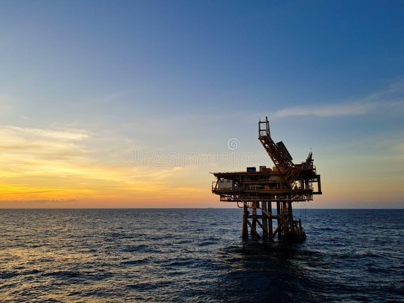 Plataforma petrolífera e por do sol imagem de stock royalty free