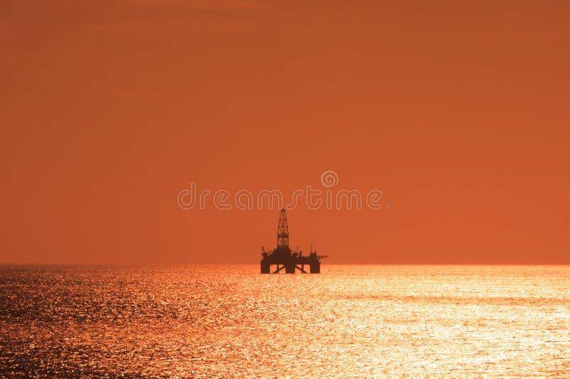 Plataforma petrolífera a pouca distância do mar durante o por do sol fotografia de stock