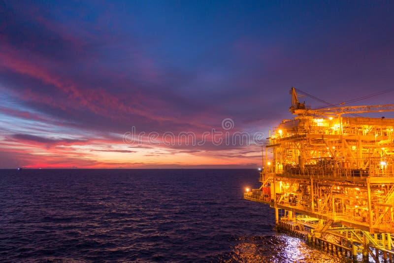 Plataforma a pouca distância do mar do equipamento de petróleo e gás com tempo bonito do por do sol ou fotografia de stock
