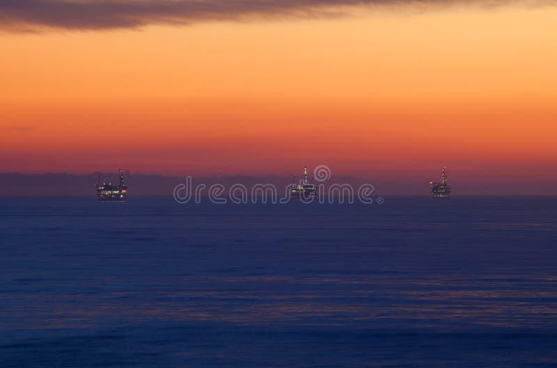 Plataformas petroleras en el mar en la puesta del sol imagen de archivo libre de regalías