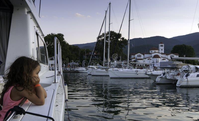 PLATAMONAS, GRÈCE - 25 août 2018 : La petite fille regarde la mer et les bateaux sur le port sur Platamonas, Grèce photographie stock libre de droits