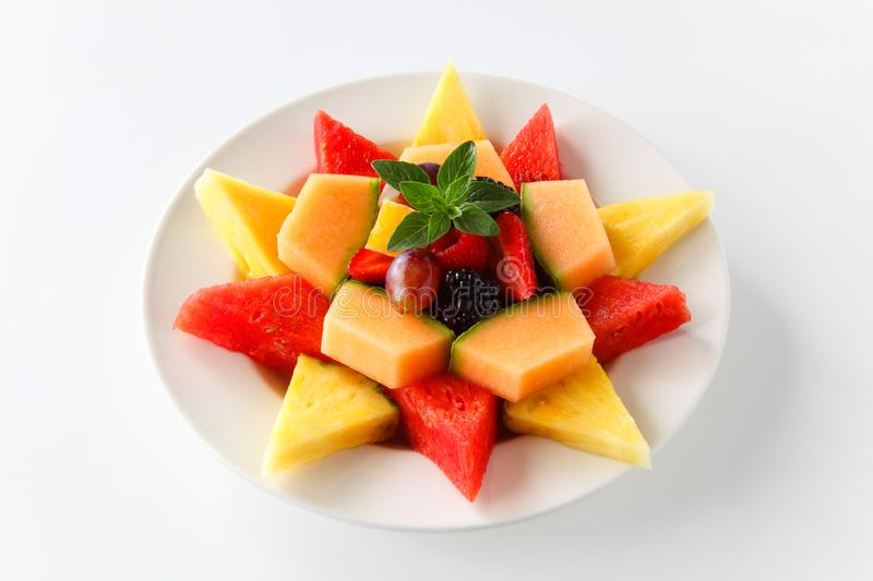 A plate of assorted fruit shaped into a star including watermelon, pineapple, cantaloupe, grapes, blackberries, strawberries, stock images
