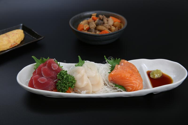 A plate of assorted sashimi. Assorted salmon, tuna, scallop sashimi made sell well as snacks of the Japanese food royalty free stock photography
