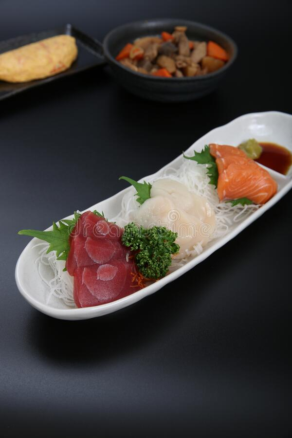 A plate of assorted sashimi. Assorted salmon, tuna, scallop sashimi made sell well as snacks of the Japanese food stock photography