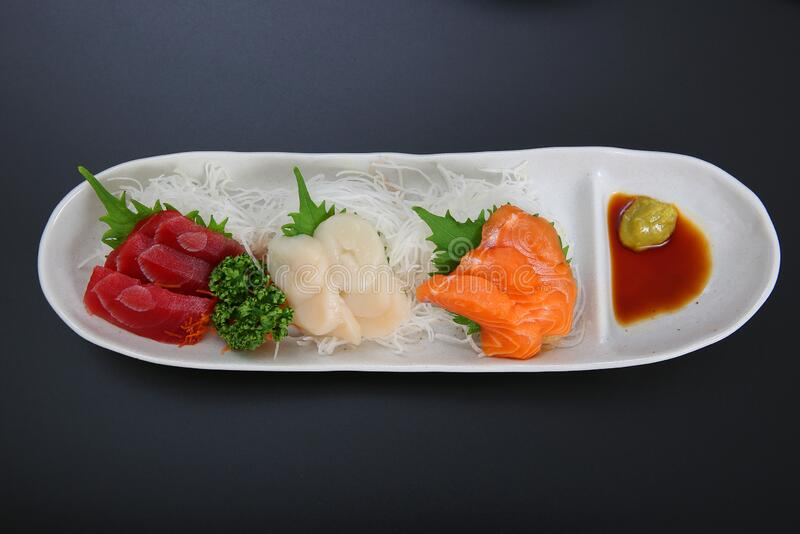 A plate of assorted sashimi. Assorted salmon, tuna, scallop sashimi made sell well as snacks of the Japanese food stock photos