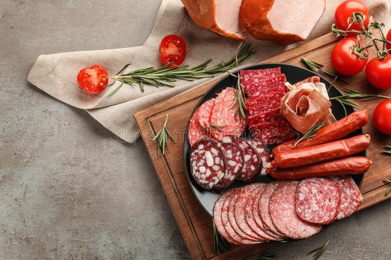 Plate with assortment of delicious deli meats on grey background royalty free stock images