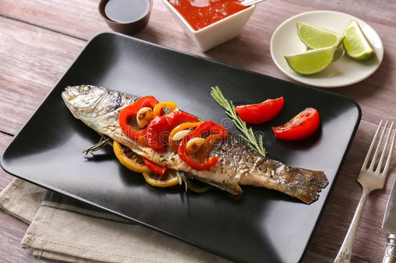 Plate with baked sea bass fish. On table royalty free stock photos