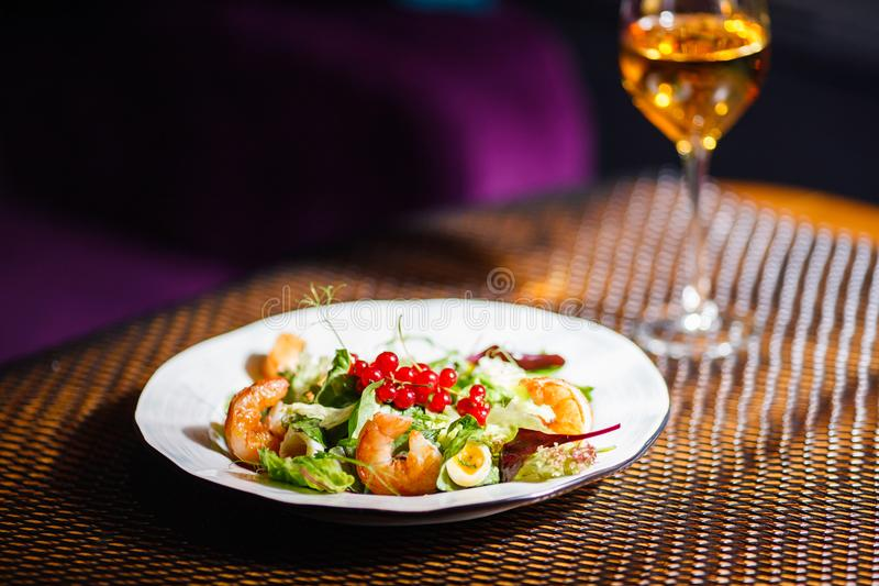 A plate with a beautiful appetizing salad of fresh vegetables, shrimps, quail eggs and lingonberries is on the table with a wine. A plate with a beautiful royalty free stock images