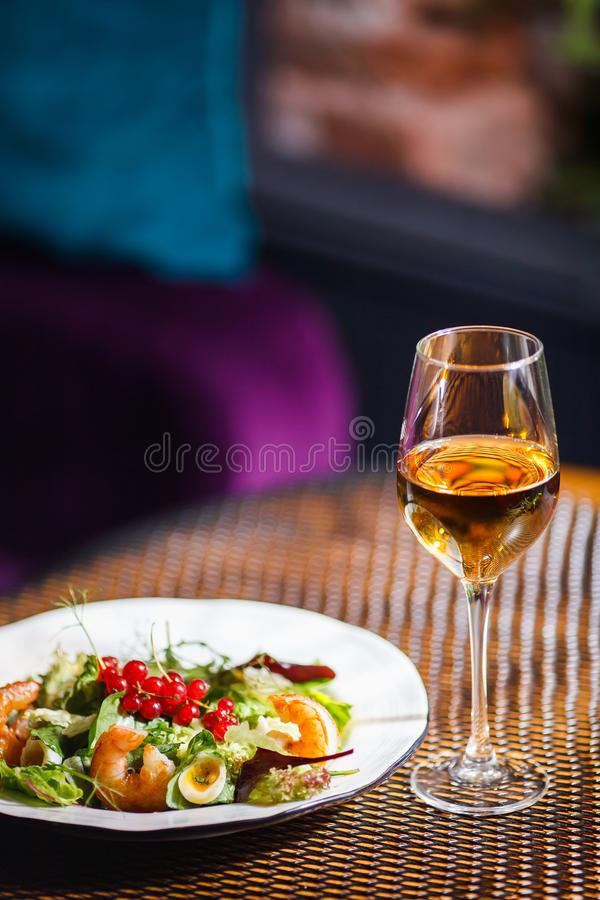 A plate with a beautiful appetizing salad of fresh vegetables, shrimps, quail eggs and lingonberries is on the table with a wine. A plate with a beautiful stock photos