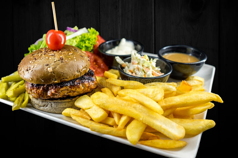 Plate with beef burger, bowl of red, white sauce, salad, golden french fries, pickles and green vegetables. stock photo