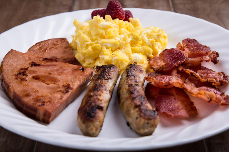 Plate of breakfast - scrambled eggs, bacon, sausage and ham 1 royalty free stock images