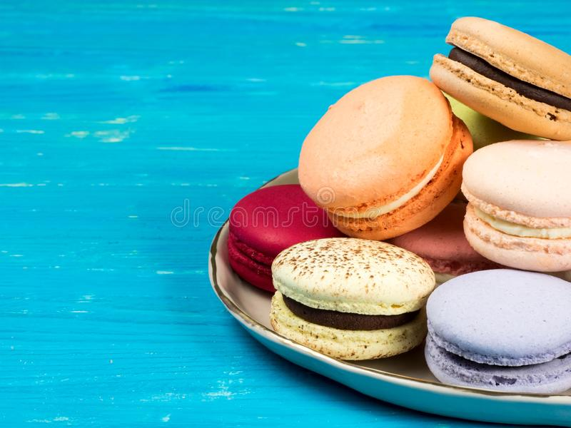 A plate of brightly colored French macarons. Traditional brightly colored French macaroons on a hand-made plate, set on a blue wooden board, close-up view with stock photography