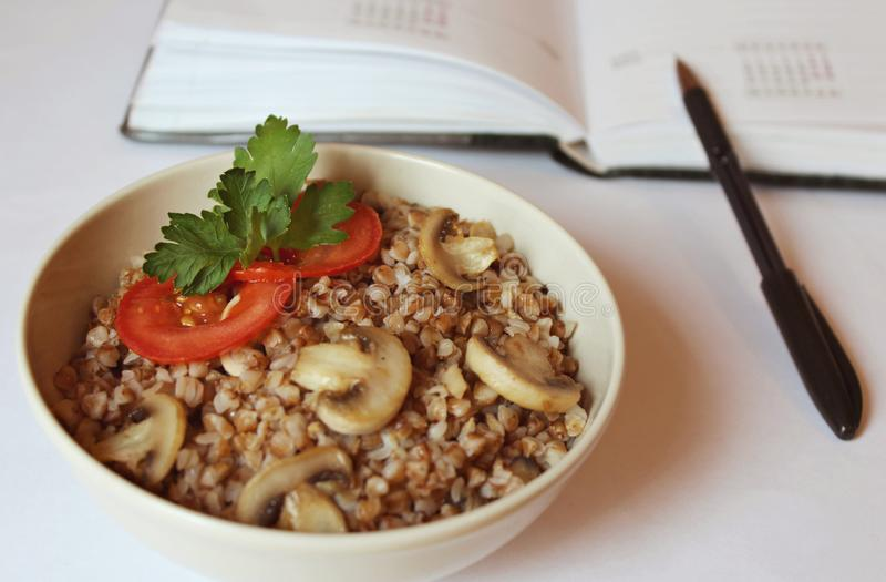 Plate with buckwheat porridge with mushrooms tomato slices and green close-up. royalty free stock photography