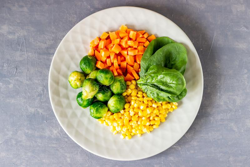 Plate with cabbage, carrots, corn and spinach. Healthy eating stock photos