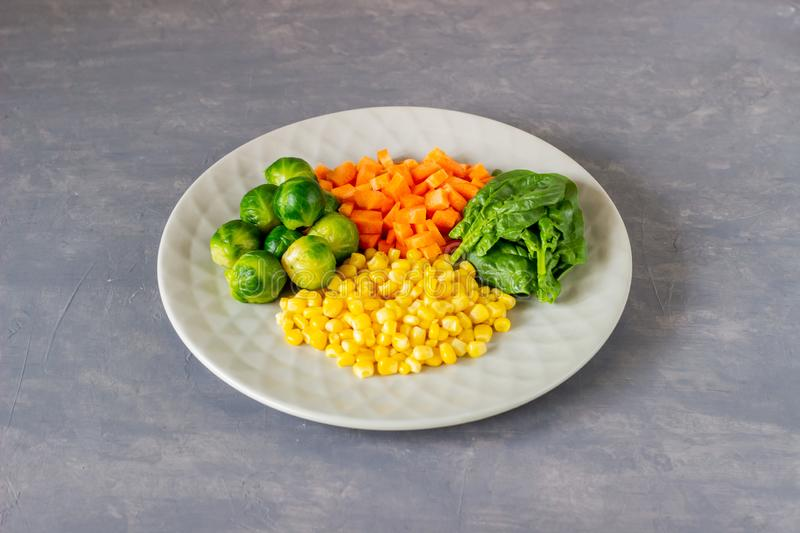 Plate with cabbage, carrots, corn and spinach. Healthy eating stock photography