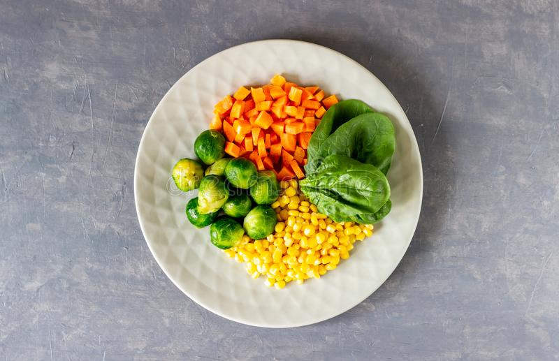 Plate with cabbage, carrots, corn and spinach. Healthy eating royalty free stock images