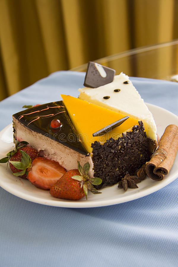 Plate of cakes on blue. Three cakes slices with various topping with fresh strawberry; photo with copy space stock photography