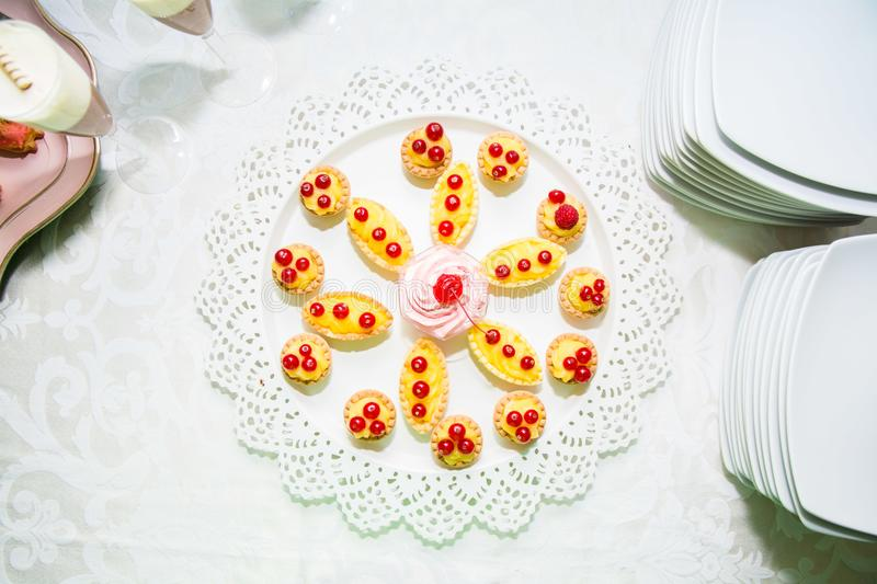 Plate with cakes. This is a plate full with berrys and cherry cakes stock photography