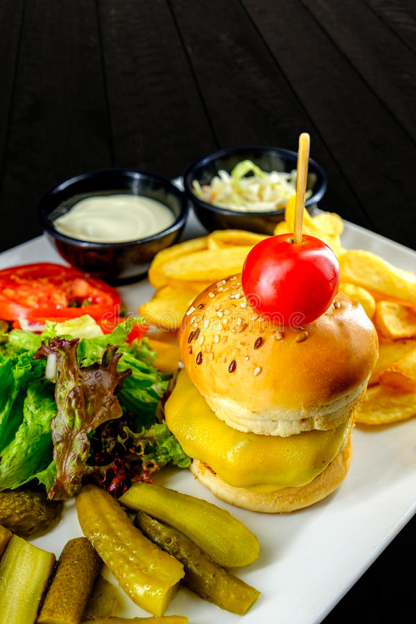 Plate with cheeseburger, french fries, tomatoes, salad and bowls of sauce. royalty free stock photo