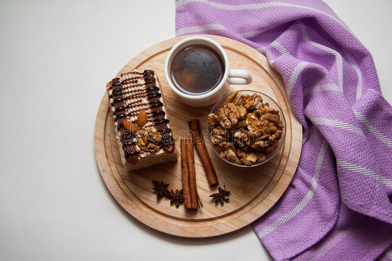 Plate with chocolate cake and coffee. Creamy chocolate cake with various nuts, a dessert for tea or coffee stock image