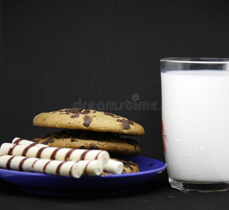 A plate of chocolate chip cookies on a blue plate with a glass of milk on a black background close-up stock photos