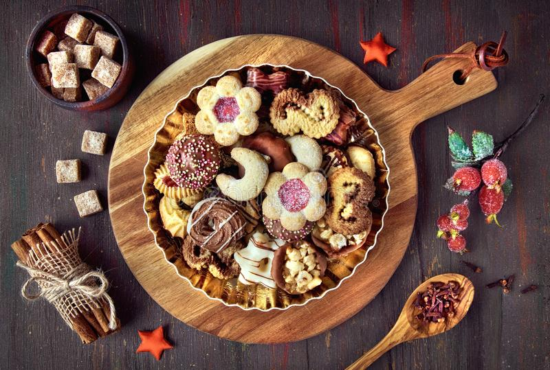 Plate of Christmas cookies on a wooden board on dark rustic back royalty free stock image