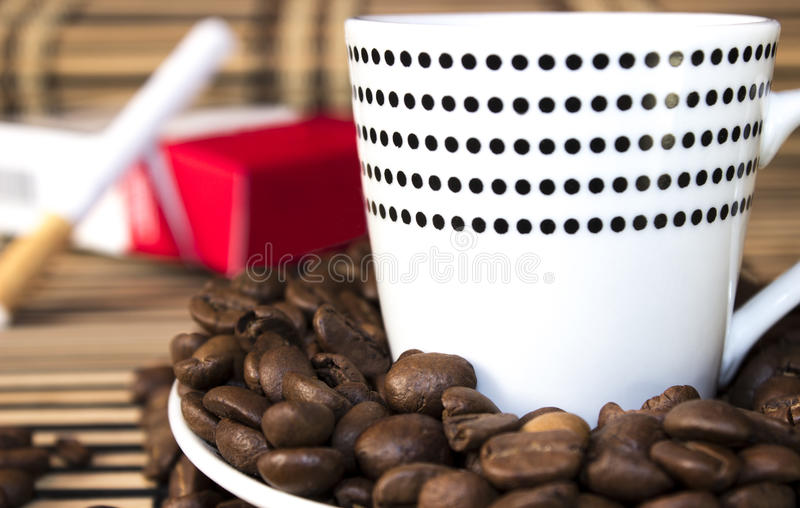 Plate with coffee beans and dotted cup in front of a cigarette. On a wooden stand. Blured royalty free stock photos
