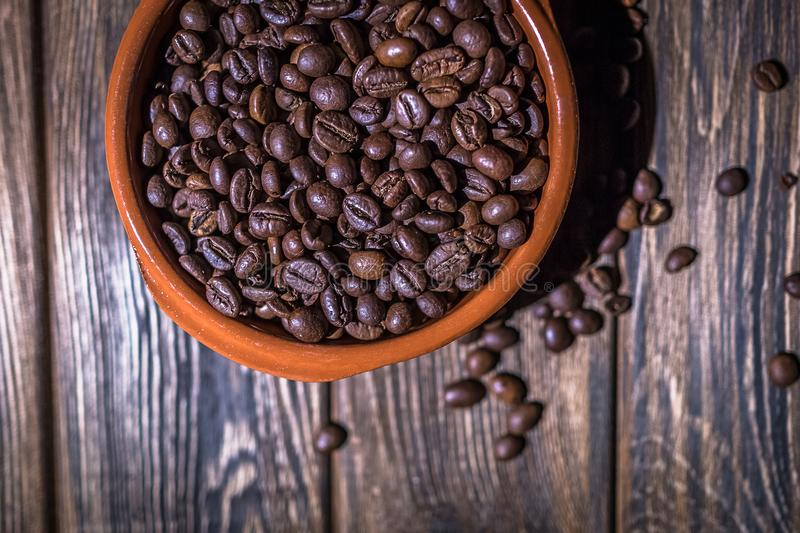 A plate of coffee beans on a wooden background. The roasted coffee beans lie in a large ceramic plate on a wooden table stock images