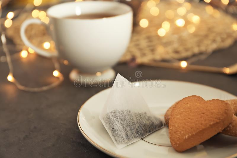 Plate with cookies and tea bag on table stock photography