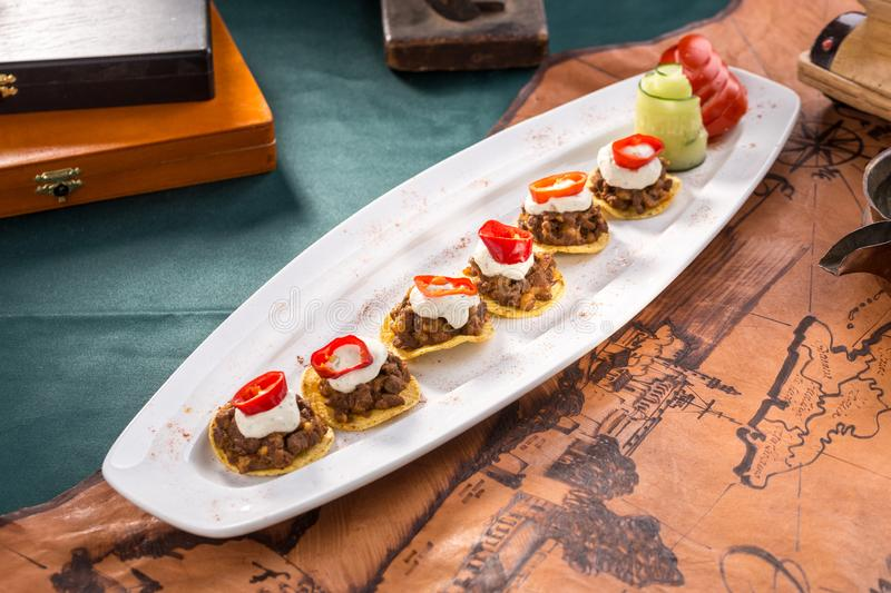 Plate of corn chips nachos with fried minced meat and cream sauce on old map background stock photos