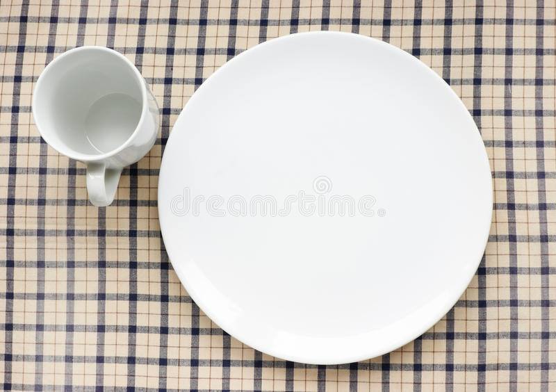 Plate and cup on tablecloth royalty free stock photo