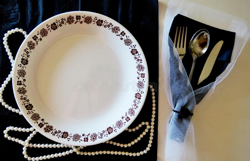Plate and cutlery on a black and white background with luxurious decoration stock images